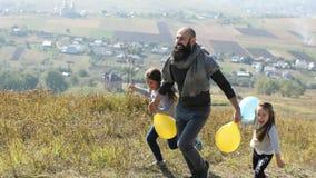 Будьте отцом с его 2 дочерьми при воздушные шары бежать в луге видеоматериал