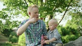 Будьте отцом с его пузырями мыла сына дуя, времяпровождением семьи потехи, ребенком имея потеху с его папой в парке лета медленно видеоматериал