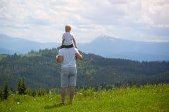 Будьте отцом с малым сыном на его плечах Горы на backg Стоковые Фотографии RF
