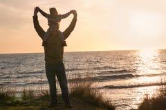 Будьте отцом с ребёнком на заходе солнца морем Стоковые Изображения