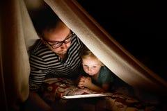 Будьте отцом с таблеткой и маленькой дочерью дома на ноче Стоковая Фотография