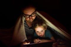 Будьте отцом с таблеткой и маленькой дочерью дома на ноче Стоковое Изображение