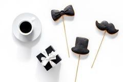 Будьте отцом торжества дня или дня рождения ` s с печеньями знака настоящего момента, черного галстука, усика и шляпы на белом по Стоковые Фотографии RF