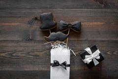 Будьте отцом торжества дня или дня рождения ` s с печеньями знака настоящего момента, черного галстука, усика и шляпы на деревянн Стоковые Изображения