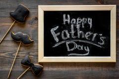Будьте отцом торжества дня или дня рождения ` s с печеньями знака черного галстука, усика и шляпы на деревянном положении квартир Стоковая Фотография RF