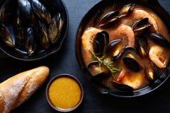 Буйабес супа морепродуктов с рыбами, креветками, мидиями томатом, омаром Деревенская темная предпосылка стиля Плоское положение Стоковое Фото