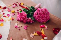2 букета украшают дырочками розы лежа на кровати вполне лепестков Стоковая Фотография