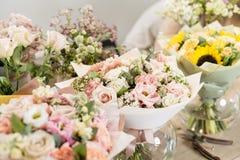 Букеты на таблице, деле флориста Цветки весны различных разнообразий свежие красивое поставки коробки предпосылки изолированное н Стоковые Изображения RF
