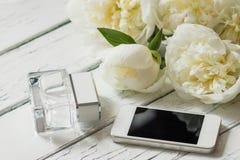Букет белых пионов, телефона и бутылки дух на деревянном столе Стоковые Изображения RF