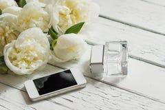 Букет белых пионов, телефона и бутылки дух на деревянном столе Стоковое фото RF
