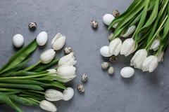 Букет белых тюльпанов и яичек цыпленка и триперсток на серой конкретной предпосылке Взгляд сверху Плоское положение Открытка для Стоковые Изображения