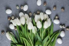 Букет белых тюльпанов и яичек цыпленка и триперсток на серой конкретной предпосылке Взгляд сверху Плоское положение Открытка для Стоковое Изображение RF