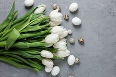 Букет белых тюльпанов и яичек цыпленка и триперсток на серой конкретной предпосылке Взгляд сверху Плоское положение Открытка для Стоковое Фото