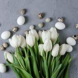 Букет белых тюльпанов и яичек цыпленка и триперсток на серой конкретной предпосылке Взгляд сверху Плоское положение Открытка для Стоковые Фотографии RF