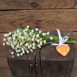 Букет белых лилий долины с зелеными лист на деревянной предпосылке Стоковая Фотография