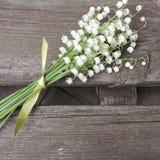 Букет белых лилий долины с зелеными лист на деревянной предпосылке Стоковое фото RF