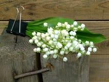 Букет белых лилий долины с зелеными лист на деревянной предпосылке Стоковые Изображения RF