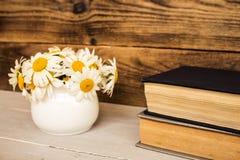 Букет белых маргариток и книг на деревянной предпосылке Стоковые Изображения