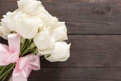 Букет белых роз на деревянной предпосылке с лентой Стоковое фото RF