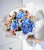 Букет владением руки женщины голубых цветков гортензии и розовых роз Стоковая Фотография