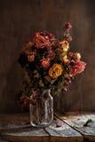 Букет высушенных роз в стеклянном опарнике на темной старой деревянной предпосылке Стоковое фото RF