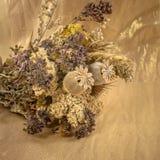 Букет высушенных цветков на предпосылке золота покрасил ткань стоковые фото