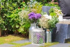Букет в стальной вазе около комплекта чая в саде Стоковая Фотография RF
