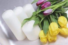 Букет желтых и розовых тюльпанов разбросан на светлую поверхность Рядом декоративные свечи конец-вверх, взгляд сверху Стоковые Изображения