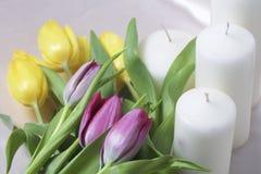 Букет желтых и розовых тюльпанов разбросан на светлую поверхность Рядом декоративные свечи конец-вверх, взгляд сверху Стоковое фото RF