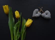 Букет желтых тюльпанов и 2 черно-белых сердец на черноте Стоковое Изображение