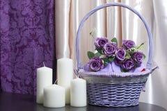 Букет желтых тюльпанов стоит в стеклянной вазе обернутой в красной ленте связанной к смычку Рядом декоративные свечи Стоковые Фото