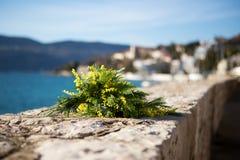 Букет желтых цветков мимозы лежит на пляже, на утесах Стоковые Изображения RF