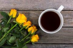 Букет желтых роз и белой чашки кофе на деревянной предпосылке Стоковые Фотографии RF