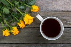 Букет желтых роз и белой чашки кофе на деревянной предпосылке Стоковая Фотография