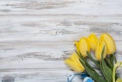 Букет желтых тюльпанов и подарка с голубой лентой на древесине Стоковое фото RF