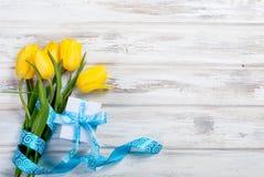 Букет желтых тюльпанов и подарка с голубой лентой на древесине Стоковые Фото