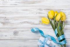 Букет желтых тюльпанов и подарка с голубой лентой на древесине Стоковое Изображение RF