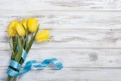 Букет желтых тюльпанов и подарка с голубой лентой на древесине Стоковые Изображения RF