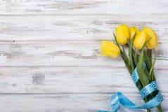 Букет желтых тюльпанов и подарка с голубой лентой на древесине Стоковая Фотография RF