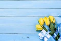 Букет желтых тюльпанов и подарка с голубой лентой на сини Стоковые Фото
