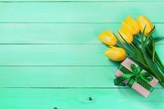 Букет желтых тюльпанов и подарка с зеленой лентой на gre Стоковое Фото