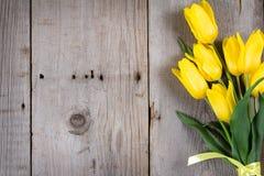 Букет желтых тюльпанов и подарочной коробки на серой деревянной предпосылке Стоковые Фотографии RF