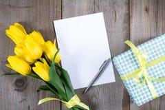 Букет желтых тюльпанов и подарочной коробки на серой деревянной предпосылке Стоковые Фото