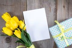 Букет желтых тюльпанов и подарочной коробки на серой деревянной предпосылке Стоковое Фото