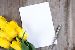 Букет желтых тюльпанов и подарочной коробки на серой деревянной предпосылке Стоковое Изображение