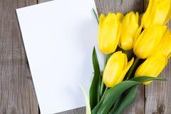 Букет желтых тюльпанов и подарочной коробки на серой деревянной предпосылке Стоковое Изображение RF