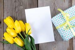 Букет желтых тюльпанов и подарочной коробки на серой деревянной предпосылке Стоковые Изображения RF