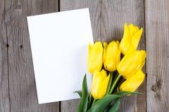 Букет желтых тюльпанов и подарочной коробки на серой деревянной предпосылке Стоковая Фотография
