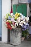 Букет искусственных цветков - желтых, красных, оранжевых лилий и голубых гортензий в ведре цинка высоком около входа к hous Стоковое фото RF