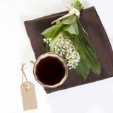 Букет лилий долины перевязанной с розовой лентой и крышка чая на белой деревянной таблице копируют космос Стоковая Фотография RF